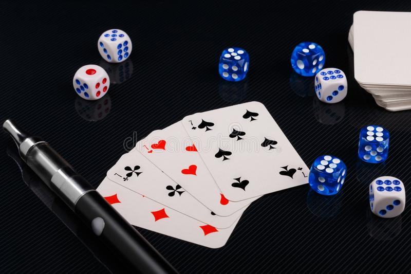 Blue and white dices and cards with electronic sigarette on black glossy background. Several blue and white dices and cards with electronic sigarette on black royalty free stock images