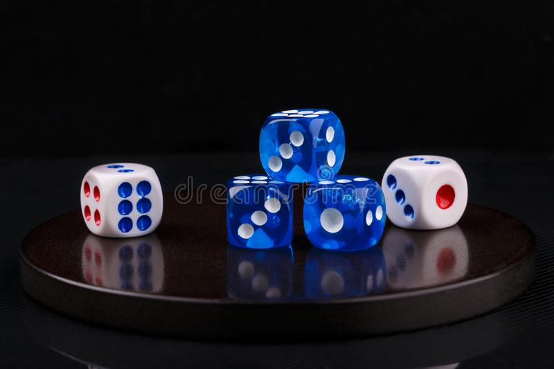 Blue and white dices on a round stone base. black background. Closeup image of several blue and white dices on round stone base stock photo