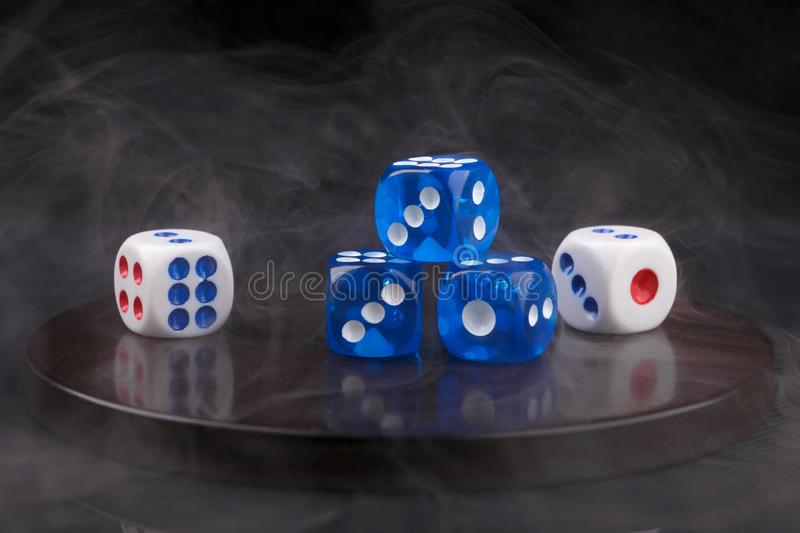 Blue and white dices on round stone base in smoke. black background. Closeup image of several blue and white dices on round stone base in smoke stock photo