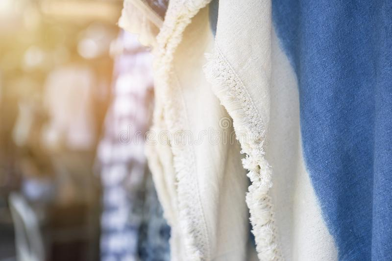 Blue and white dress hanging at the market with vintage warm light. Fashion and textile business concept royalty free stock images