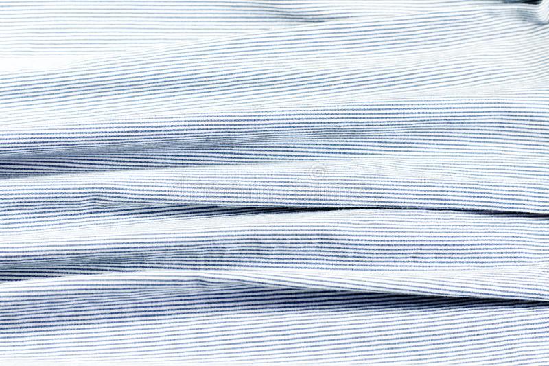 Blue and white fabric with stripes. Crumpled blue and white fabric with stripes as background stock image