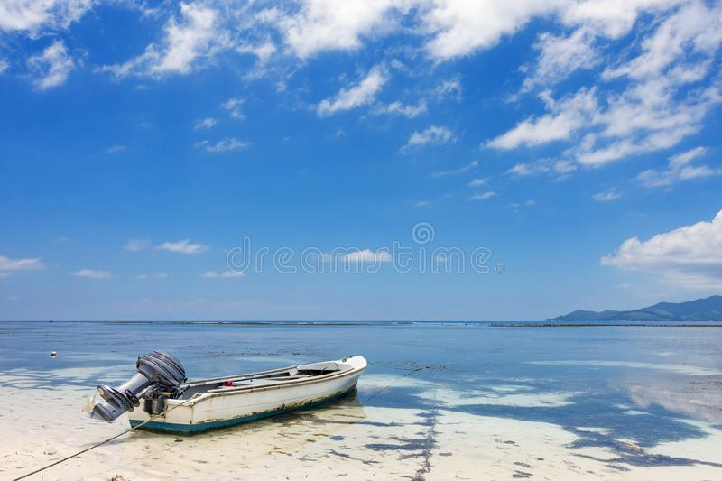 Blue white fishing boat on tropical beach royalty free stock image