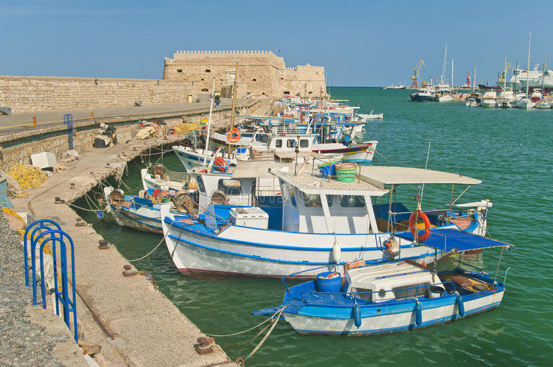 Blue and white fishing boats with medieval fortress stock image
