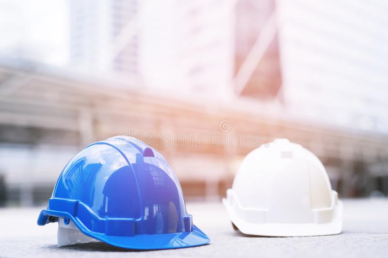 Blue and white hard safety wear helmet hat in the project at construction site building on concrete floor on city. helmet for work. Man as engineer or worker stock photography