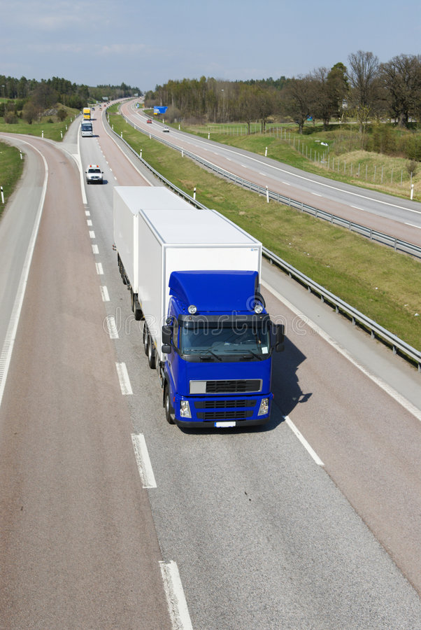 Blue and white lorry on highway stock photography