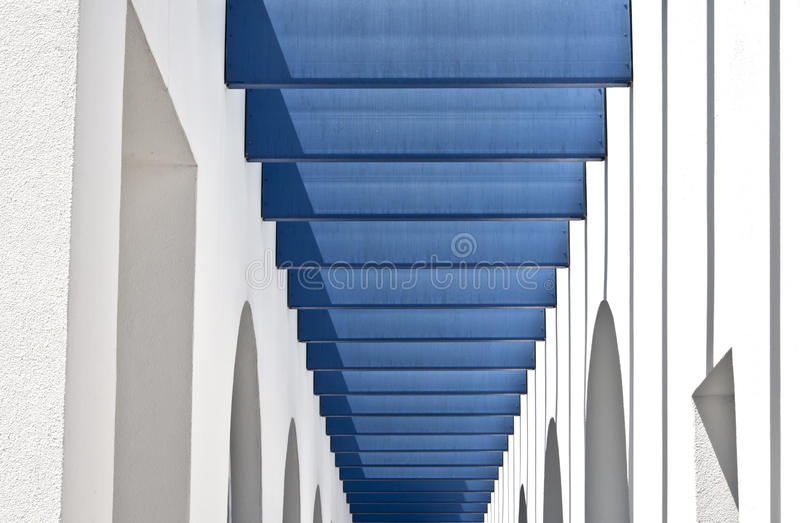 Blue and White Modern Building. A abstract design is formed by the blue, white and grey patterns of the walls, overhangs, and shadows of a modern building royalty free stock images