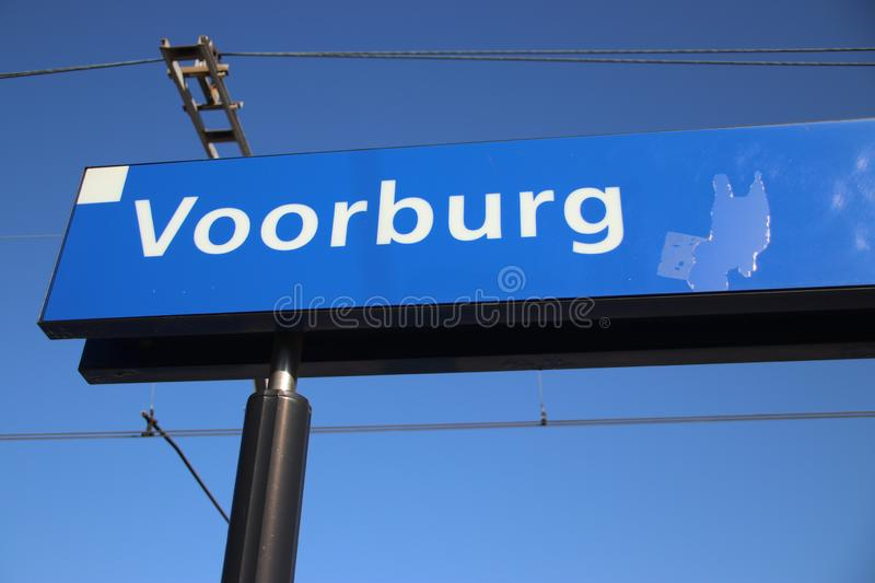 Blue and white name sign Voorburg on the platform of the railway station in the Netherlands. royalty free stock photography