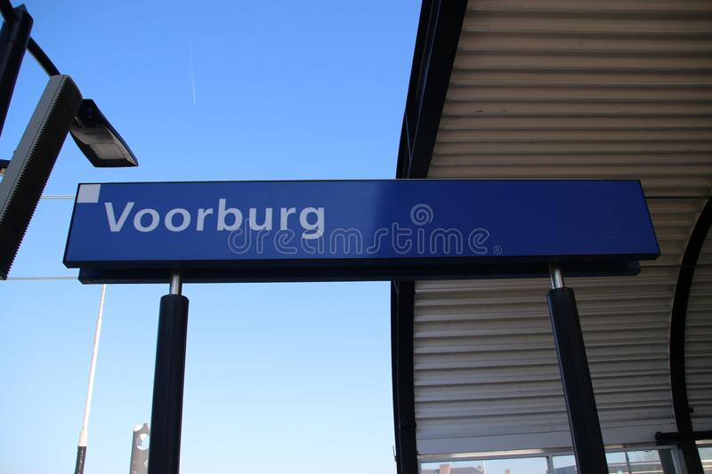 Blue and white name sign Voorburg on the platform of the railway station in the Netherlands. royalty free stock image