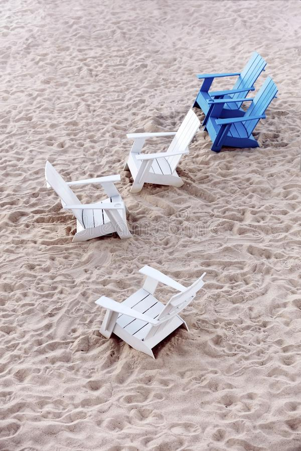 Blue and white plastic deck chairs on the sands of a beach stock images