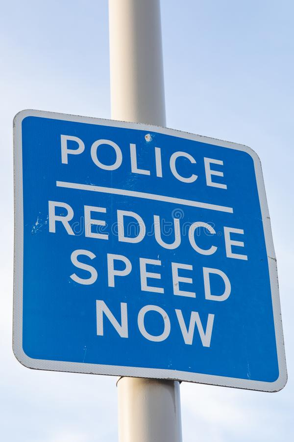 Blue and white pole mounted police reduce speed now sign St Annes on Sea Fylde Coast February 2019. Blue and white pole mounted police reduce speed now sign on royalty free stock photography