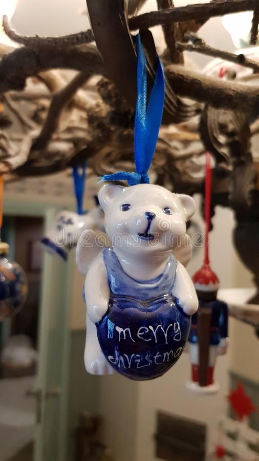 Blue and white porcelain Christmas ornament in shape of cute white teddy bear is hanging on blue ribbon. Winter holiday backdrop. New Year`s eve concept royalty free stock images