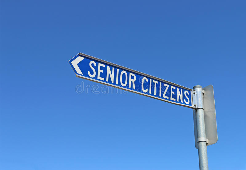 Blue and white senior citizens sign pointing. In a cloudless blue sky royalty free stock photography