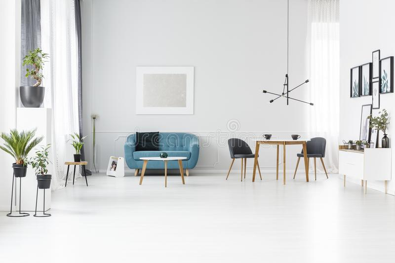 Blue and white spacious interior. Blue sofa against white wall with silver painting in spacious living room interior with table royalty free stock image