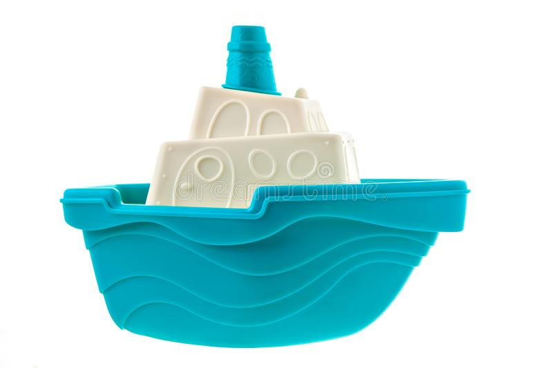 Blue and white toy boat. Isolated on white background. On the es of the ship there are waves. Above the cabin is a blue chimney stock photos