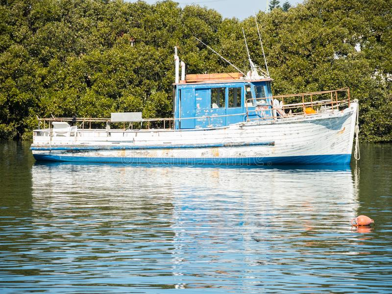 Blue and white wooden fisherman boat in the port alone at Cook River, Sydney, Australia. royalty free stock photography