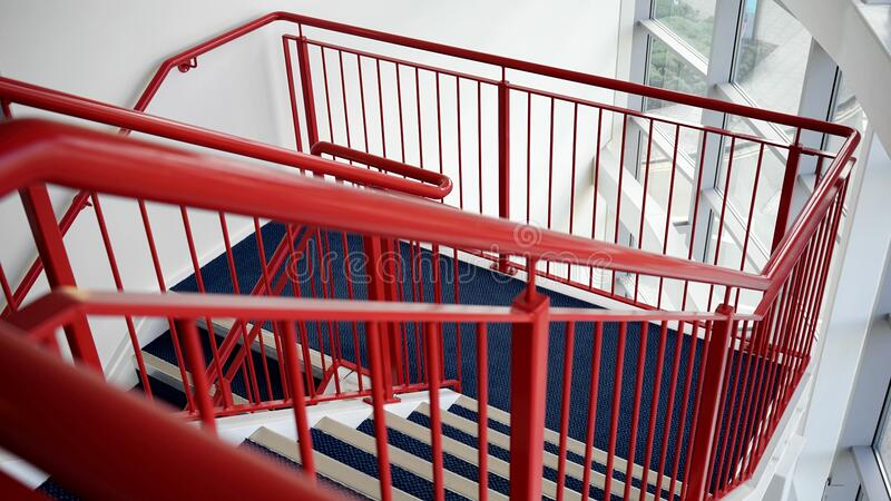 Blue and White Wooden Stairs With Red Metal Handrails stock photos