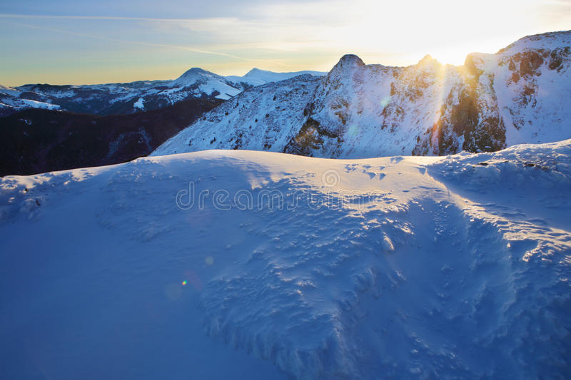Blue-and-white world. Sunrise in the Carpathian mountains. The slopes of the mountains lit by the morning sun stock images