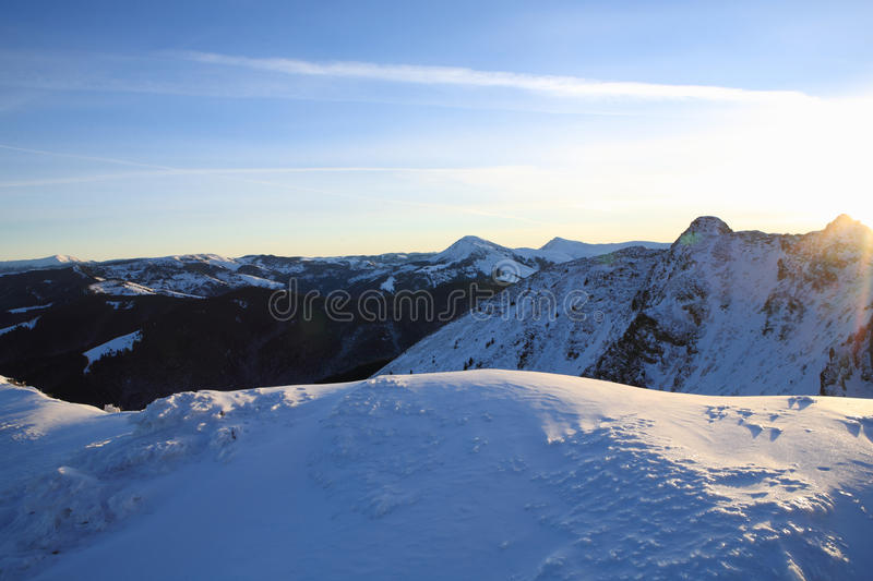 Blue-and-white world. Sunrise in the Carpathian mountains. The slopes of the mountains lit by the morning sun stock photos