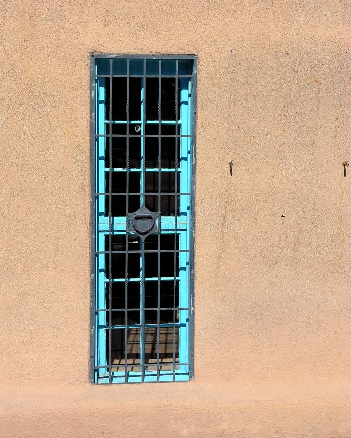 Blue window with bars on an adobe wall stock photography