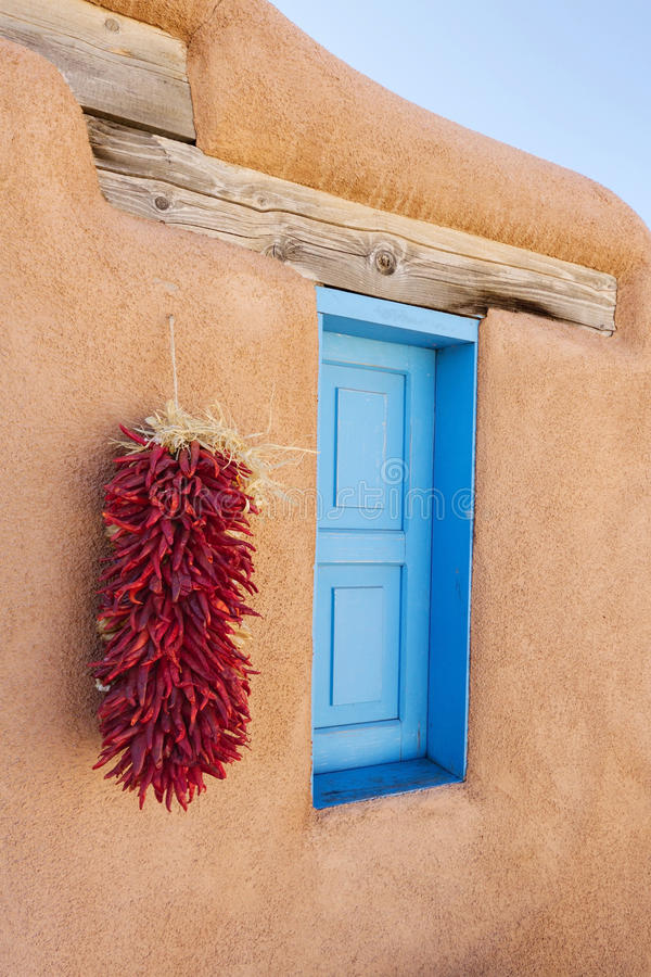 Southwestern Adobe Window. Blue window and chili pepper ristra on adobe wall, New Mexico royalty free stock image