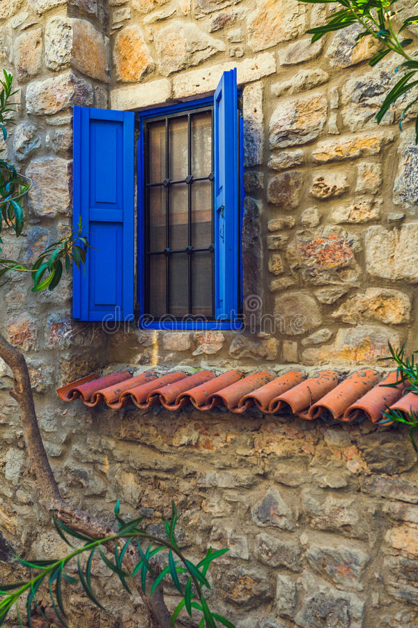 Blue window in an old stone house royalty free stock images