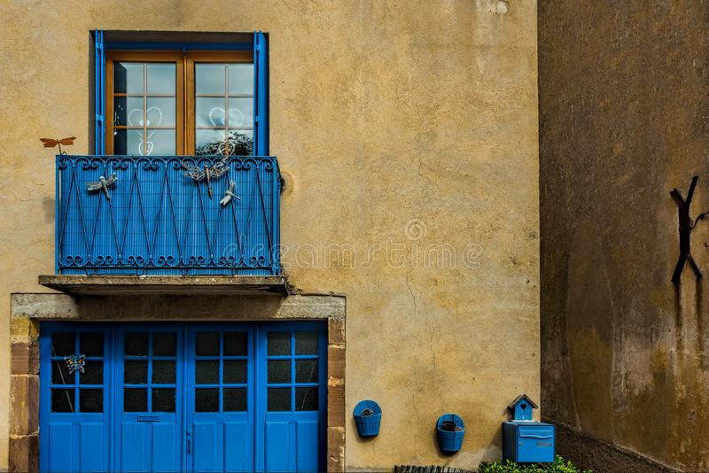 Blue windows and doors on pale yellow walls of a small town in F stock photos