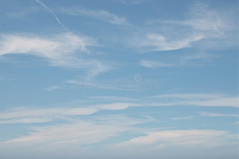 Blue windy sky with clouds background stock images