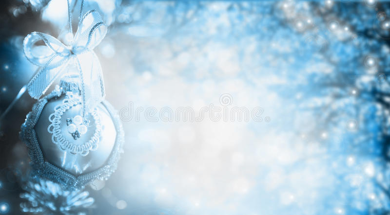 Blue Winter Christmas background with tree, branches and bauble, holiday border. Banner for website royalty free stock photography