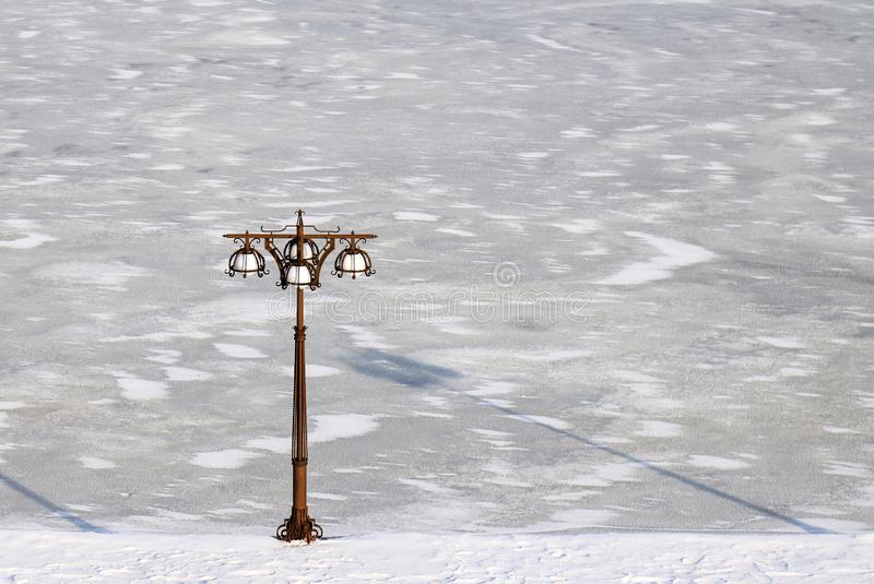 Blue winter cityscape of a river covered with ice and embankment with vintage metal lantern, Dnepropetrovsk, Ukraine. Blue winter cityscape of a river covered royalty free stock photos