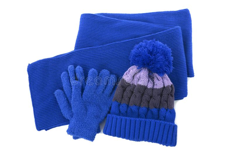 Blue winter knitted bobble hat, scarf gloves isolated white background. Blue winter knitted bobble hat, scarf gloves isolated stock photos