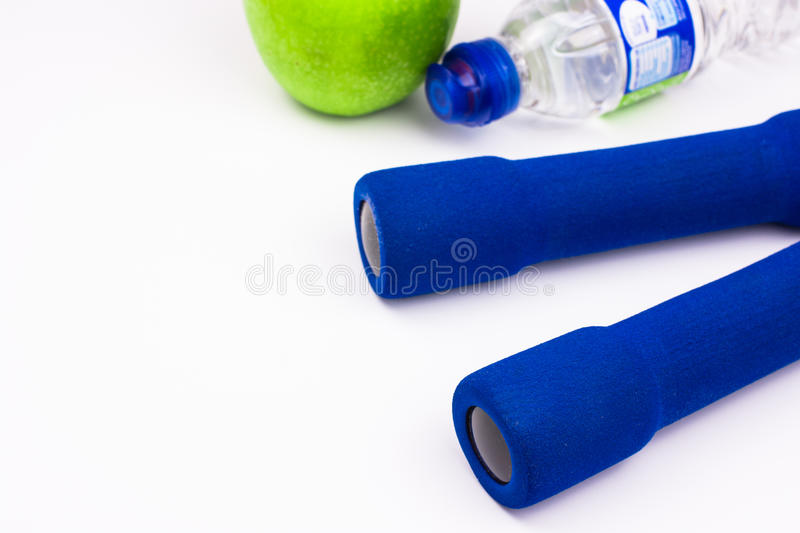 Blue women`s dumbbells with a bottle of water and a green apple on a white gym floor, copyspace for text stock images