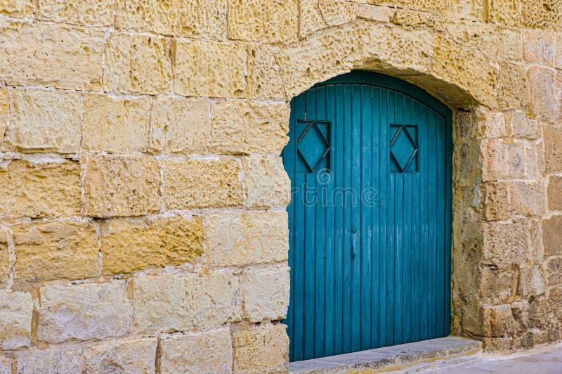 Blue wood door inset into stone wall in Malta stock photo