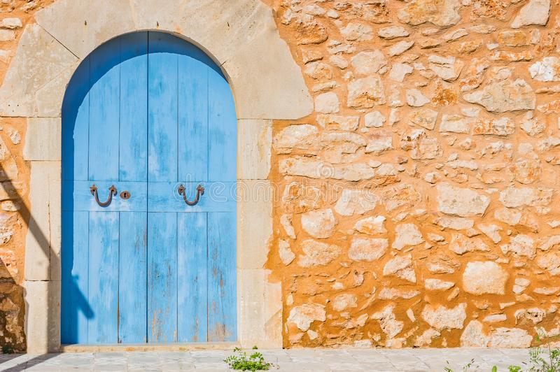 Blue wood door and rustic stone wall of mediterranean house royalty free stock photo