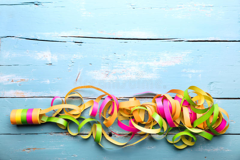 Blue wooden background, colorful streamers, concept kids birthday stock photo