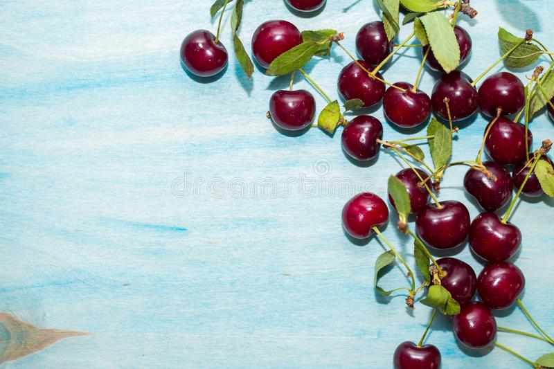 Blue wooden background for the label, with the edge of a red ripe cherry, close-up stock image