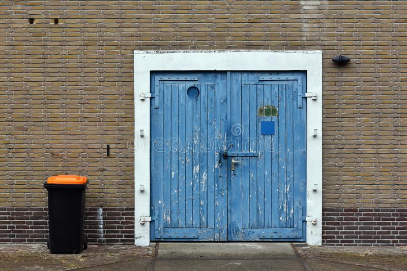 Blue wooden barn doors. Waste container next to a blue wooden barn doors of a Dutch warehouse royalty free stock photo