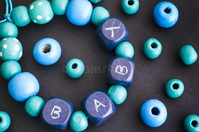 Bracelet of wooden beads with letters BABY on black background. royalty free stock photos