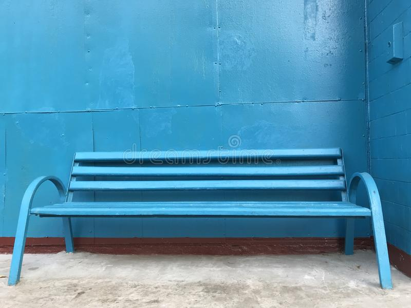 A blue wooden bench with iron legs stands on a gray concrete floor against a blue iron wall. It can serve as a background for further work, and self stock image