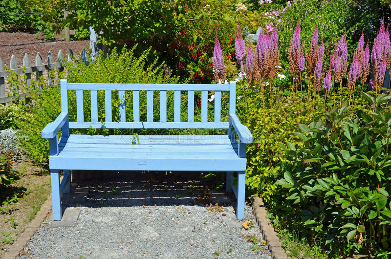 Blue garden bench. Blue wooden bench in summer garden stock photo