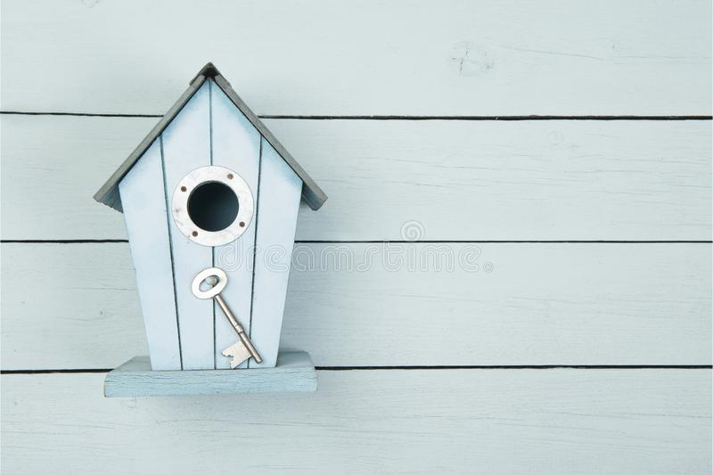 Blue wooden bird house with a metal key on a blue wooden background with copy space as a concept for a new home royalty free stock images
