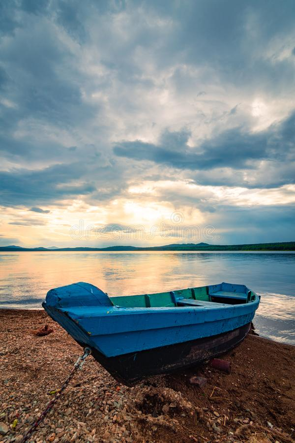 Blue wooden boat moored on the shore of lake under cloudy sky at sunset. Blue boat moored on the shore of lake under cloudy sky at sunset, background, bank, bay royalty free stock photography