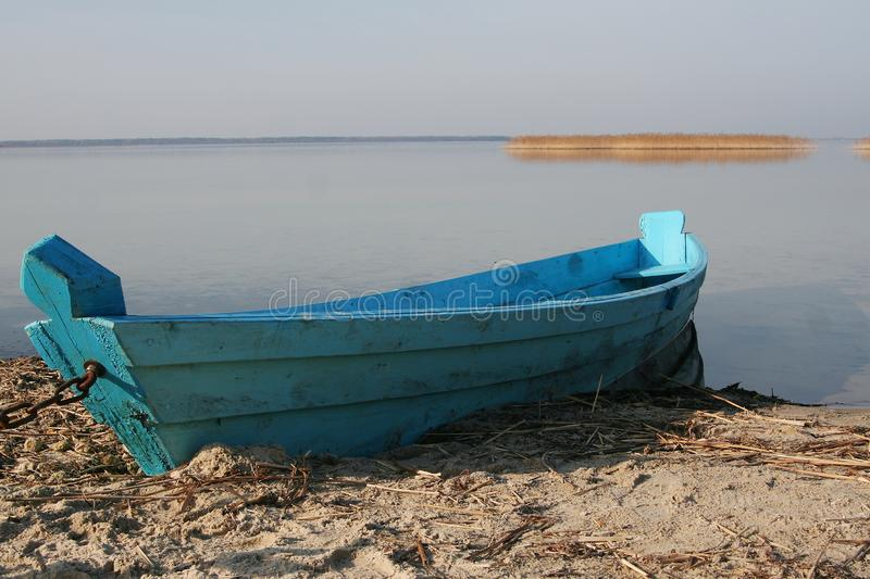 Blue wooden boat on the sandy shore against the lake stock image