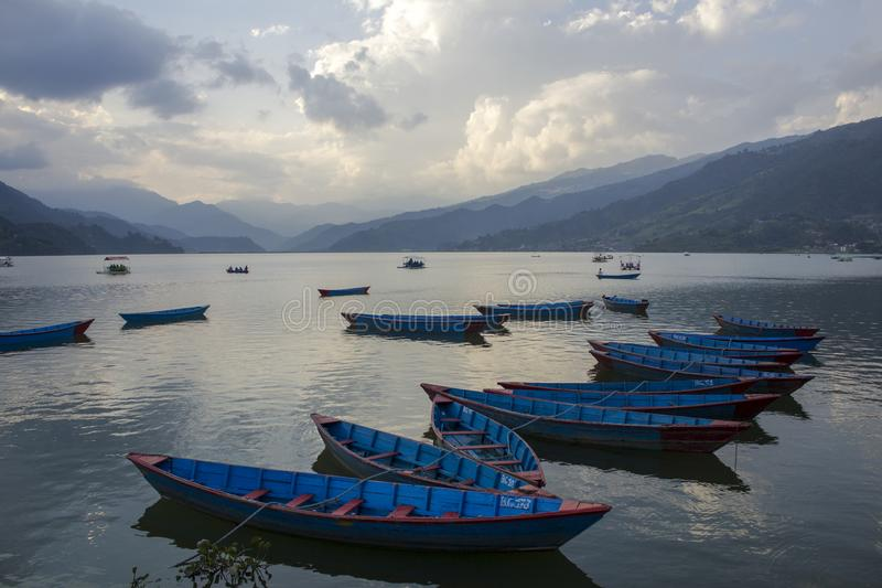 A blue wooden boats on the water against the backdrop of the lake and the mountain valley. people in pleasure boats in the evening stock images