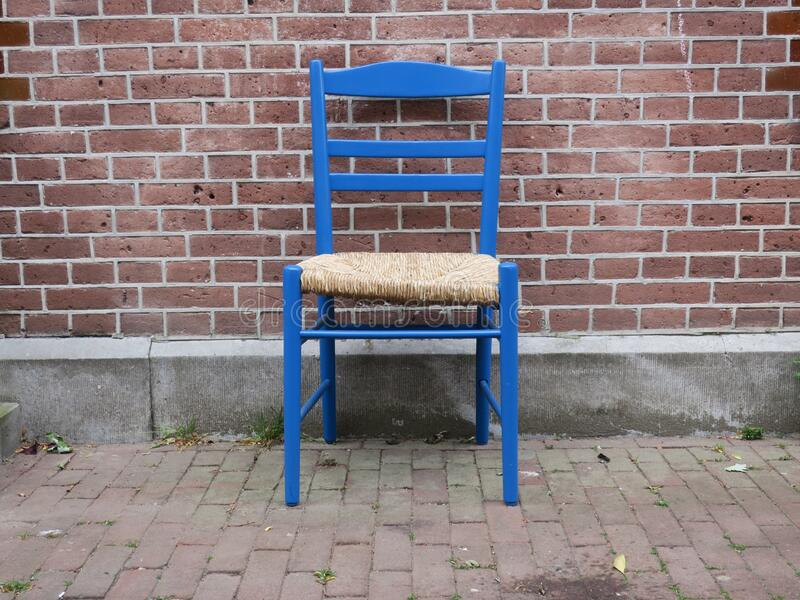 Blue wooden chair  on the sidewalk in front of a red brick wall stock photo