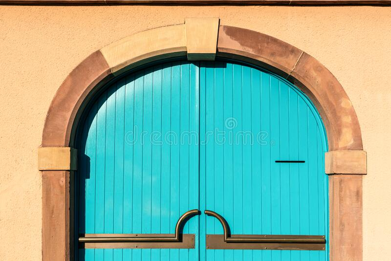 Blue wooden door on brick cement wall background stock photo