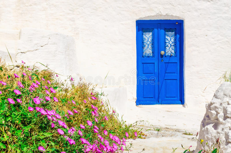 Blue wooden door, white wall and flowers, Greece. Iconic blue wooden door against clear white wall and colorful flowers. Typical view for Greek islands, Greece royalty free stock image