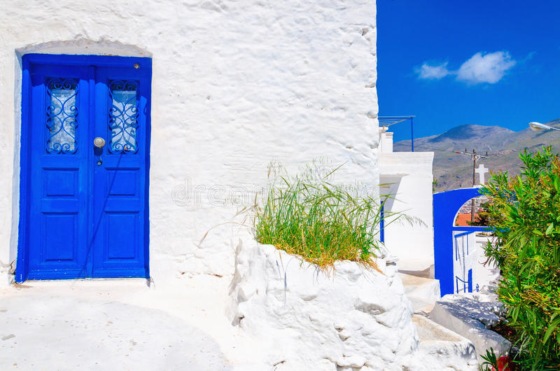 Blue wooden door, white wall and flowers in Greece. Iconic blue wooden door against clear white wall. Typical view for Greek islands, Greece royalty free stock image