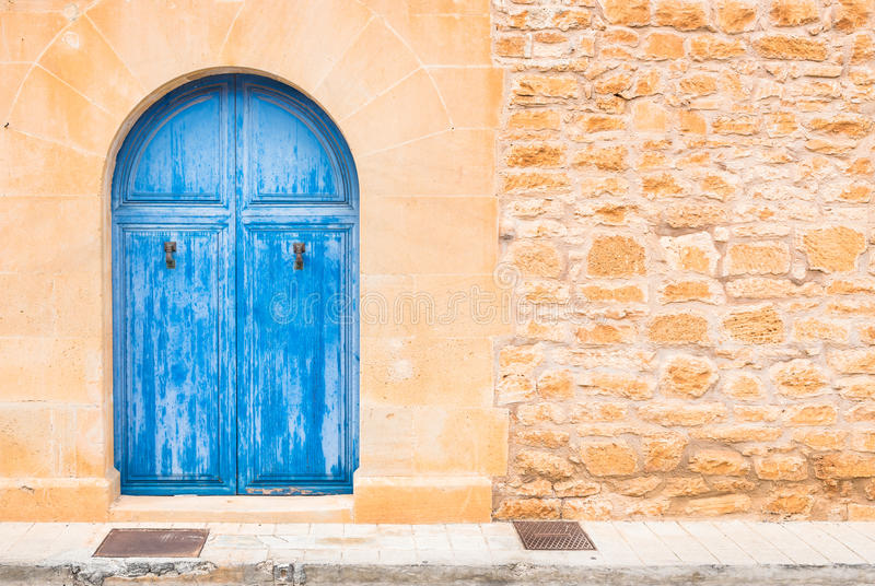 Blue wooden front door. View of an wooden blue front door with stone doorway arch and rustic stone wall stock photo