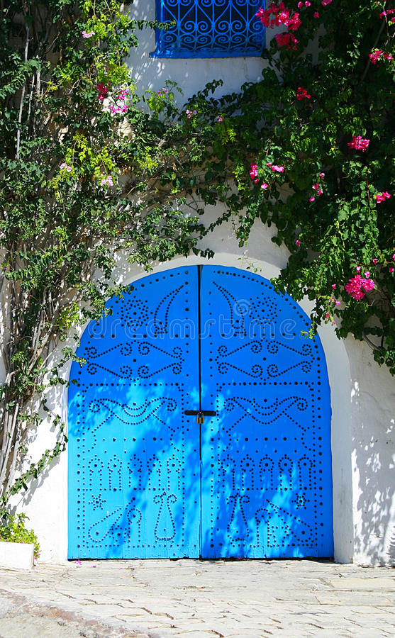Blue wooden garage gate in tunisian arabic style. This picture represents the front garage gate in tunisian arabic style located in beautiful place Sidi Bou Said royalty free stock images