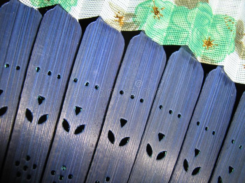 Blue wooden hand fan with colorful fabric royalty free stock photos